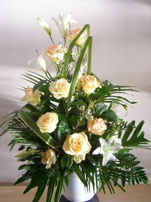 Picture of Salmon pink  sympathy flower arrangement in a white vase