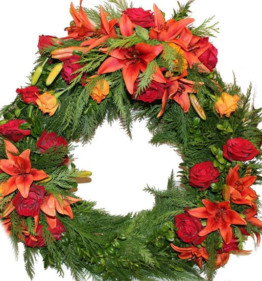 Picture of Funeral Wreath with burst of orange and red colored flowers elegantly arranged in 3 groupings -3 sizes.