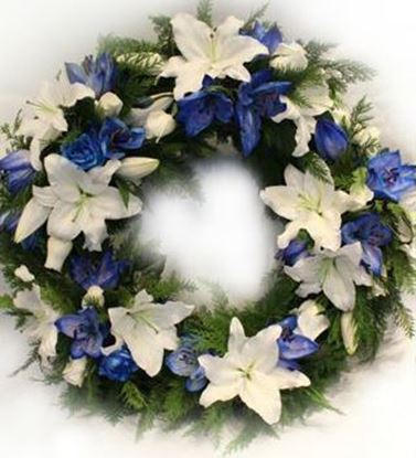Picture of Fully decorated Funeral Wreath with white and blue an Icelandic lilies, roses and more.