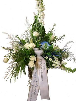 Picture of Special sympathy white flower arrangement in a white container with a tough of blue gerberas