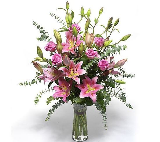 Picture of Pink long stemmed roses and oriental pink lilies in a bed of eucalyptus leaves.