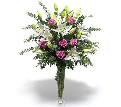 Picture of Pink long stemmed roses and oriental white lilies in a bed of eucalyptus leaves.