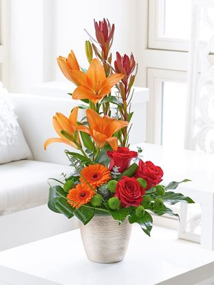 Picture of Lily, red roses, germini and lots of greenery  arranged in a ceramic vase.