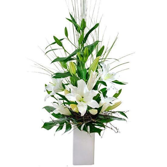Picture of Modern oriental lily flower arrangement in high vase with tropical leaves.