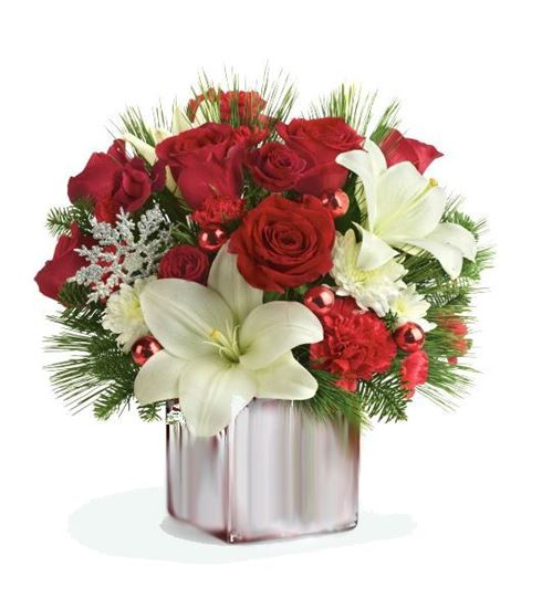 Picture of Christmas flower arrangement with red roses and white lilies in ceramic vase.