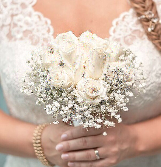 Picture of Wedding bouquet with white roses tucked in a bed of baby´s breath.
