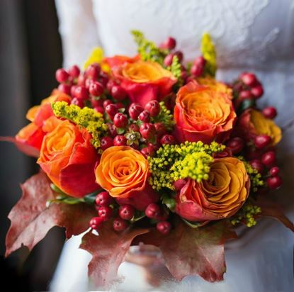 Picture of Fall Wedding bouquet with roses, hypericum berries, solidago and leaves.
