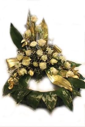 Picture of Danish style of  Funeral wreath sitting on the floor with white and gold flowers and greenery.
