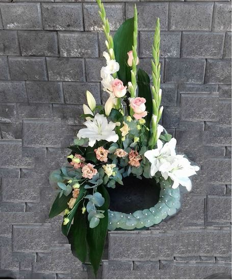 Picture of Danish style of Funeral Wreath standing on the floor with  white and pink flowers.