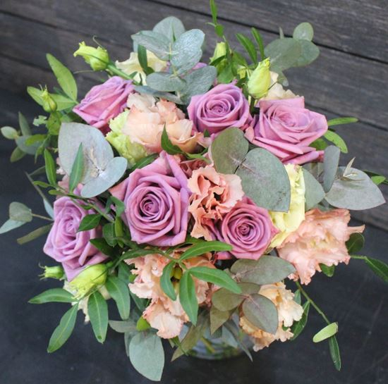Picture of Wedding bouquet with of lilac pink roses, peachy pink eustoma, greenery.