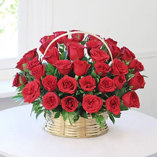 Picture of Icelandic red roses 30-60 or 100 pcs. and matching greenery in willow basket for any occasion.