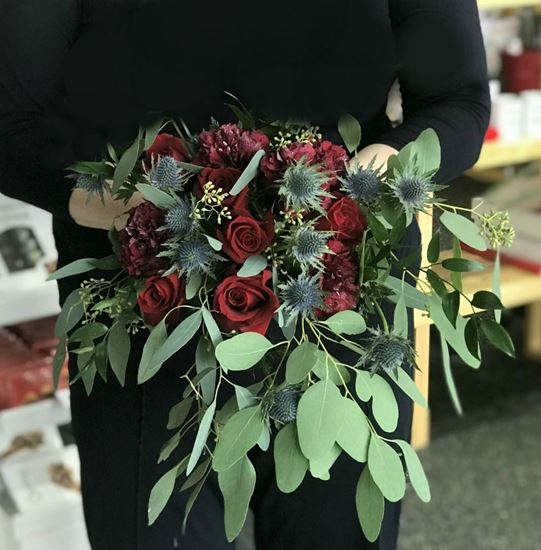 Picture of Boho style  bouquet with roses, carnations, ruskus, eryngjum and eucalypthus.