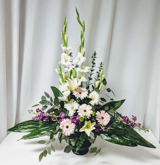 Picture of Classic display of white flowers and greenery arrangement  in vase.