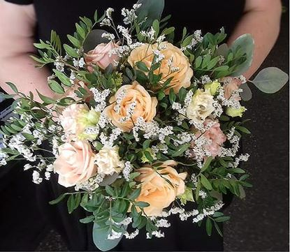 Picture of Wedding bouquet with a blend of peachy, pink and cream blooms.