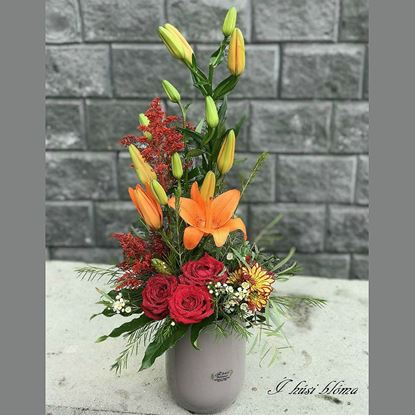 Picture of Lily, red roses, mums and lots of greenery arranged in tall colored vase.