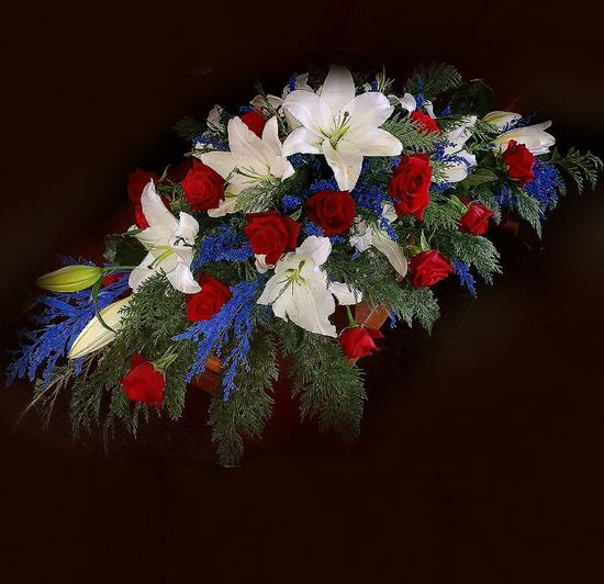 Picture of An elegant casket spray in 3 sizes with white lilies, red roses, blue solidago and more.