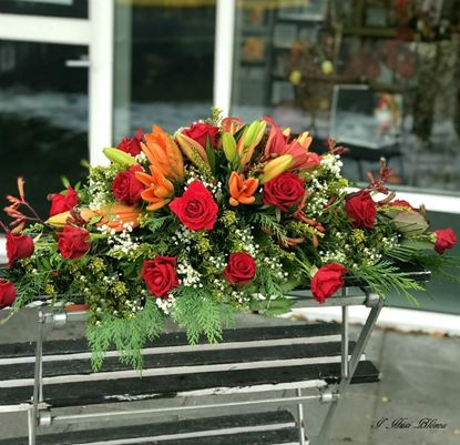 Picture of An elegant casket spray in 3 sizes with orange lilies, red roses, solidago and more.