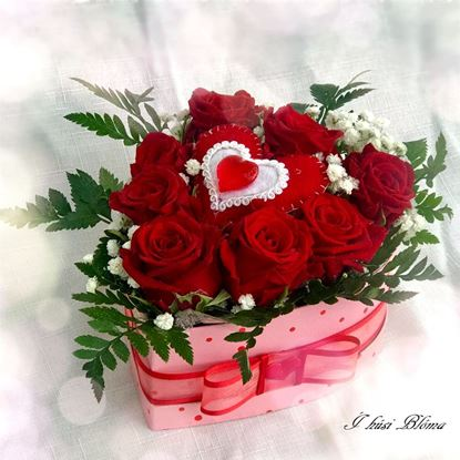 Picture of An elegant rose and other flowers arrangement in pink heart shaped box .