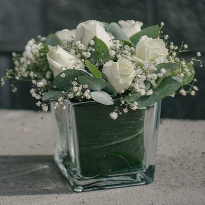Picture of An elegant  white roses, baby breath, eucalypthus -flower arrangement in vase.