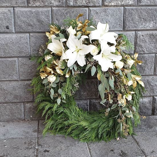 Picture of Serenity Funeral Wreath with white blooms elegantly arranged in a bed of gold leaves and greenery.