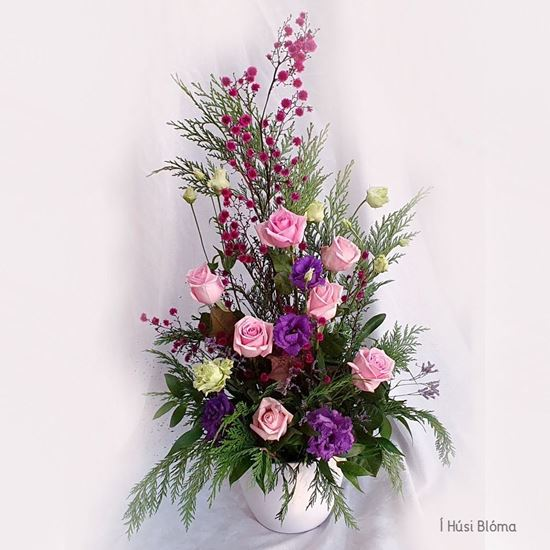 Picture of Tall pink roses and purple lisianthus flowers arrangement in a white ceramic vase with oasis foam.