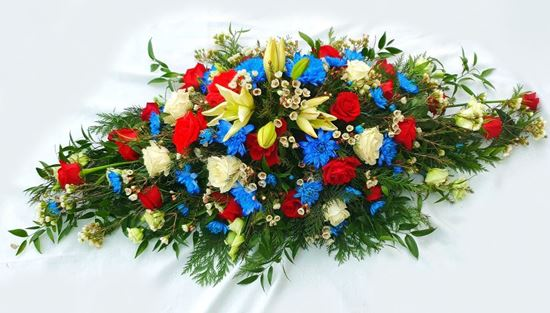 Picture of An elegant casket spray in  with white lilies, red and white roses, blue chrysanthenum and more-2 sizes.