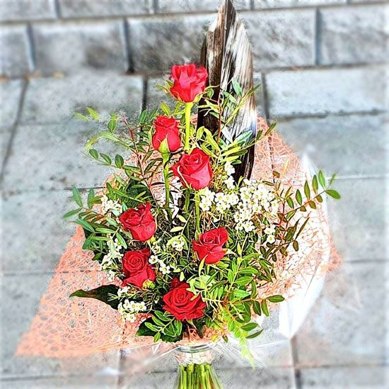 Picture of Absolutely stunning spiral bouquet with long and shorter red roses, wax flower, and lots of greenery.