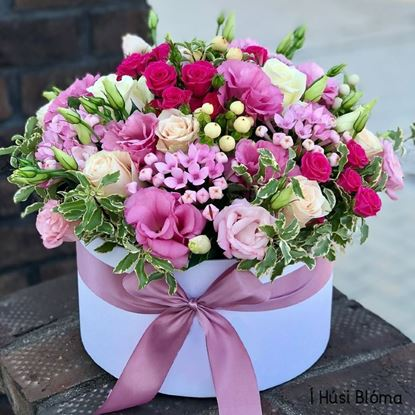 Picture of Very romantic and  elegant arrangement with roses and lots of other flowers in round hat box with ribbon.