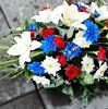 Picture of Funeral tribute flower arrangement with white, blue and red flowers and greenery in oasis base.